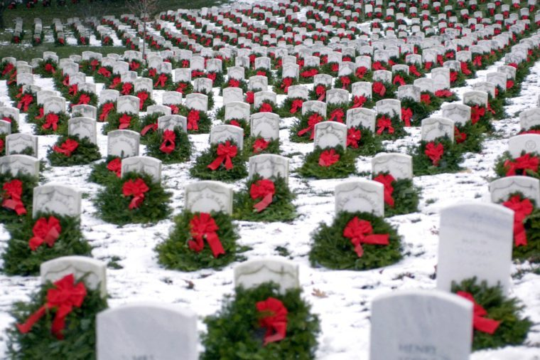 Thousands of Christmas wreaths are nestled against headstones in Section 27 at Arlington National Cemetery. Hundreds of volunteers gathered at Arlington to place more than five thousand donated Christmas wreaths on headstones in the cemetery.