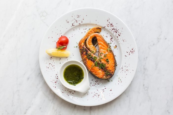 Salmon steak with herbs, lemon, tomato and salsa sauce on a plate. top view.