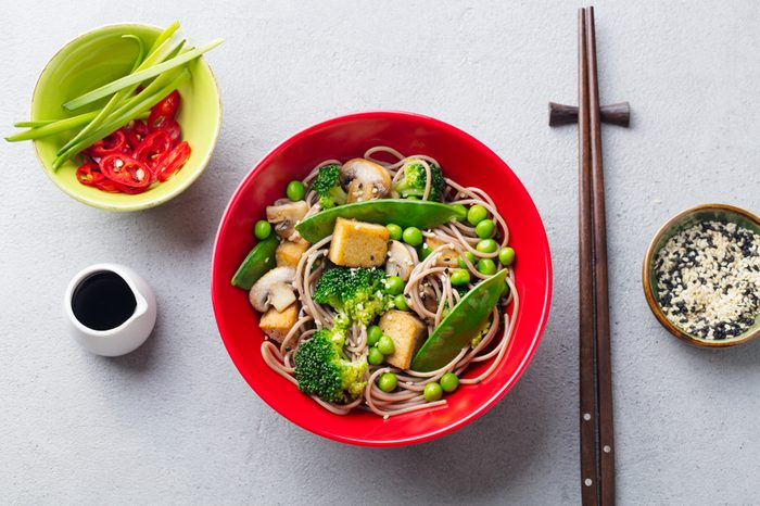 Soba noodles with vegetables and fried tofu in a bowl. Top view. Grey background.