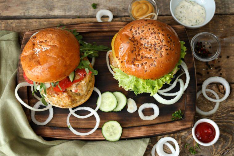 Tasty turkey burgers on wooden board