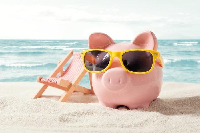 Piggy bank with sunglasses on a beach next to a beach chair