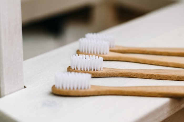 A family set of four wooden toothbrushes on white wooden background