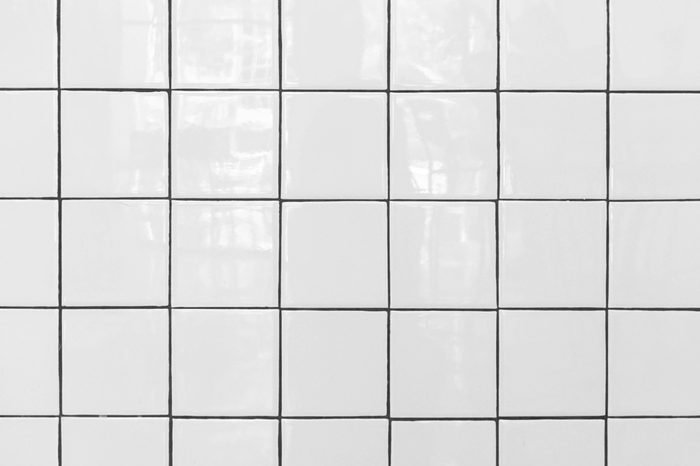 White tiles floor. Closed up of white glossy ceramic brick tiles floor texture, tile pattern in a bathroom