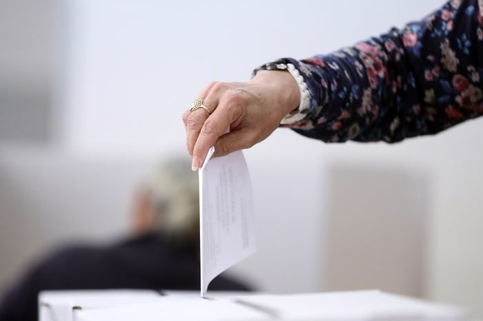 Woman hand casts a ballot as she votes for the local elections at a polling station. Focus on hand.