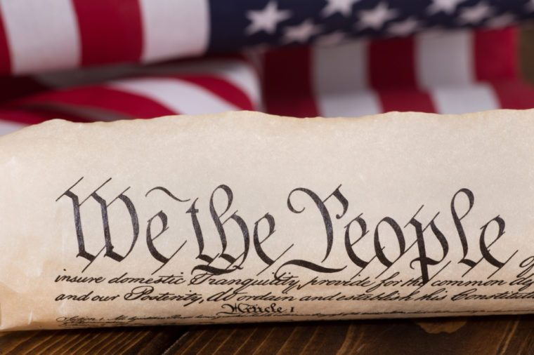 "Document text ""We the People"" of the preamble to the United States constitution with american flag in background"