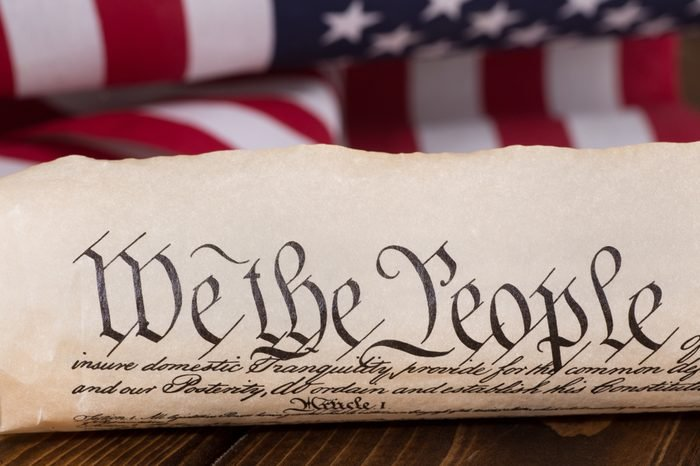 """Document text """"We the People"""" of the preamble to the United States constitution with american flag in background"""
