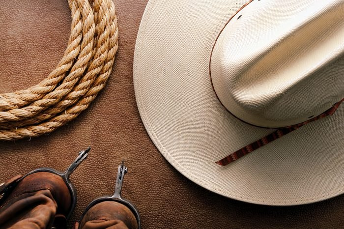 American West rodeo cowboy traditional white straw hat with roping lasso rope and vintage western riding spurs on brown leather boots over hide background