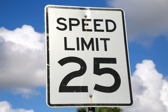 Speed Limit 25 Mph Sign on a Bright Sunny Morning with Fluffy Clouds in the Background