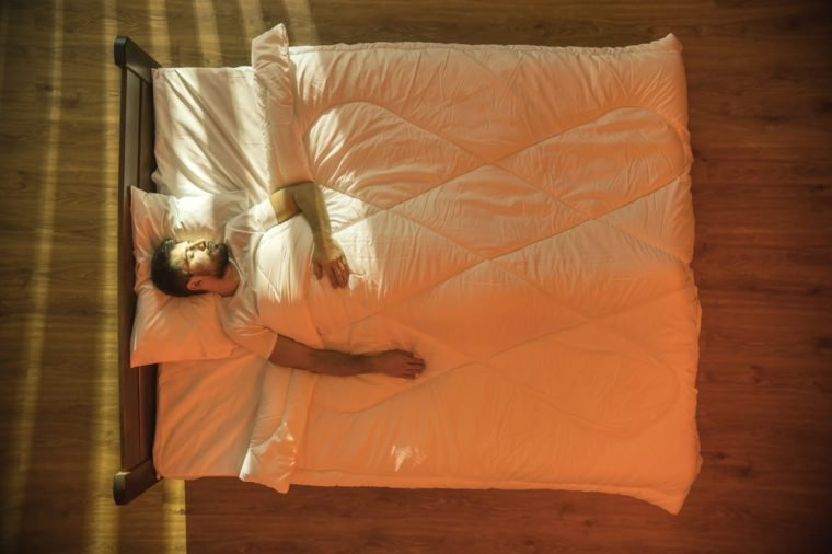 The attractive man sleeping on the bed. View from above