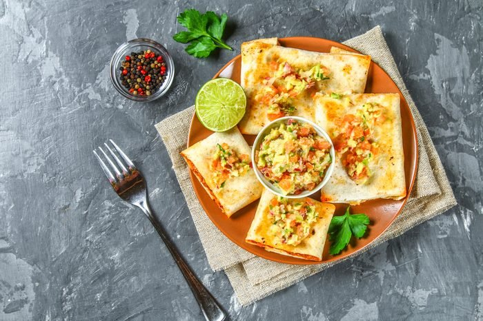 Traditional Mexican dish - chimichanga. Corn cake with minced meat, pepper, onion, garlic, oregano, zira and guacomole sauce from avocado