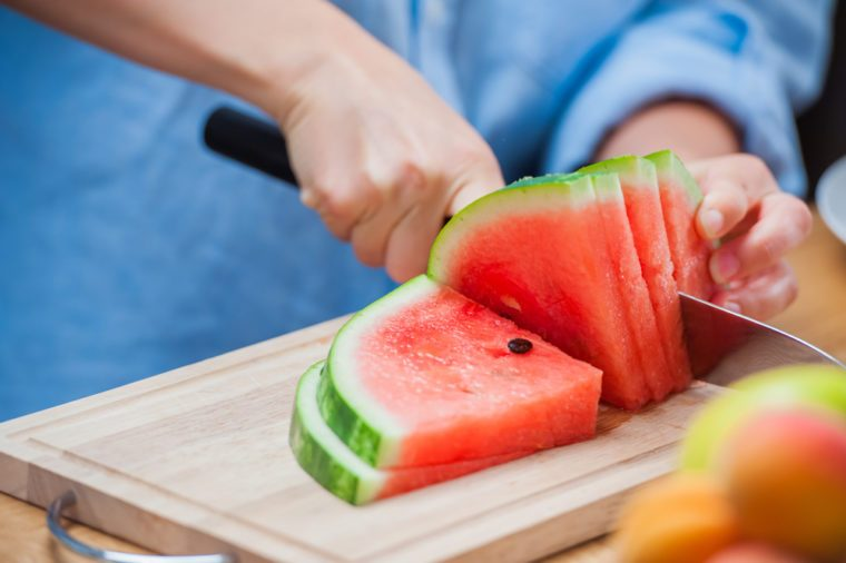 woman cutting watermelon into pieces on a wooden board