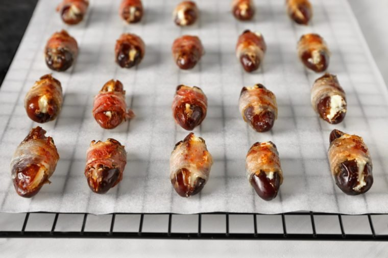 Bacon wrapped dates on baking rack, closeup