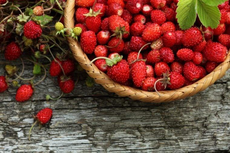 Wild strawberry basket on wooden background