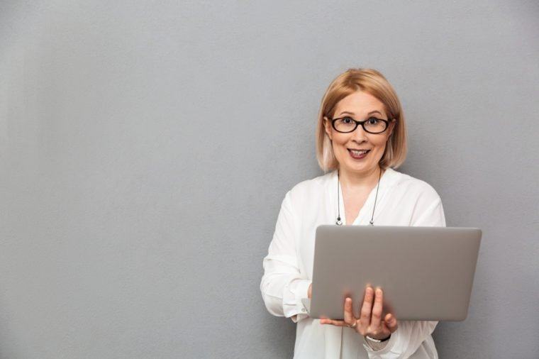 Smiling middle-aged blonde woman in shirt and eyeglasses holding laptop computer while looking at the camera over grey background