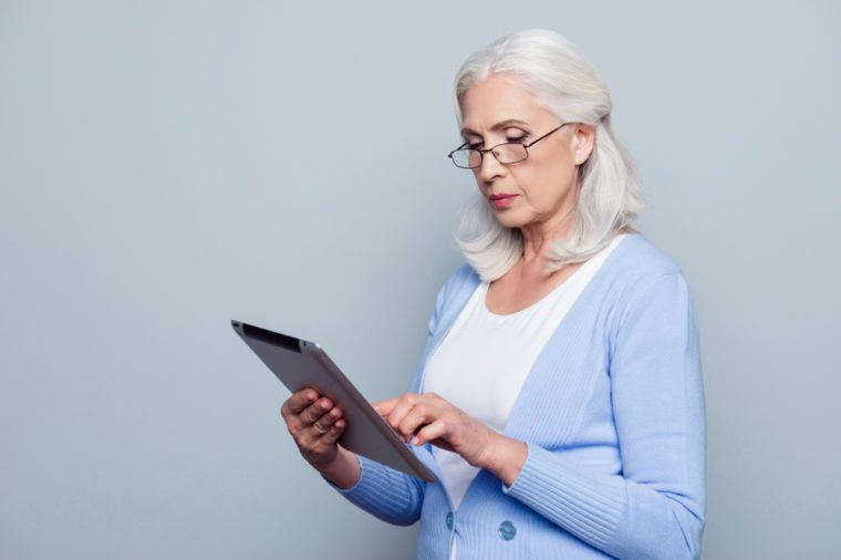 Portrait of pretty, charming, aged woman with holding tablet, using wifi internet for work, checking email, standing over grey background