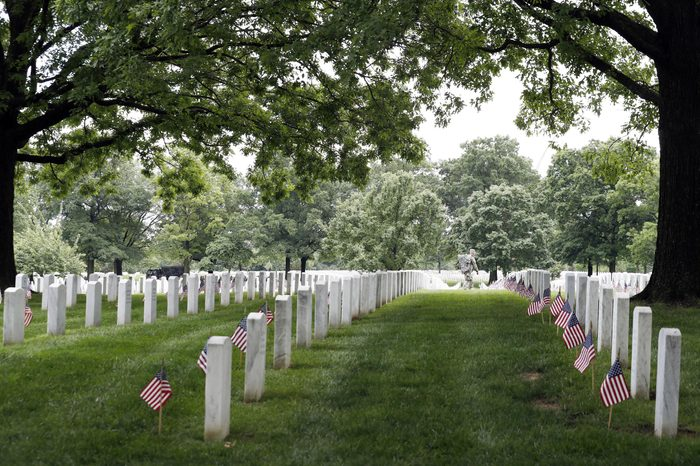 """A soldier of the 3d U.S. Infantry Regiment (The Old Guard) walks through headstones as he works during """"Flags In,"""" at Arlington National Cemetery, in Arlington, Va. Soldiers are placing nearly a quarter of a million American flags at the headstones in the cemetery in a Memorial Day tradition"""