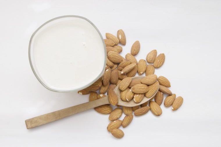 Almond milk in glass with nuts isolated on white background