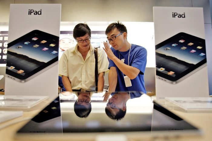 An employee of an Apple store introduces the Apple's iPad to a customer at the store during the launch of the device in Beijing