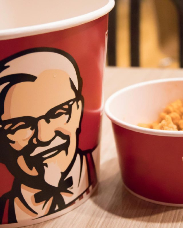 BANGKOK, THAILAND - MARCH 26, 2018: KFC, Kentucky Fried Chicken Food: Chicken Nuggets Bucket, French Fries and Cheese Sauce. KFC is a Worldwide Famous American Fast Food Restaurant. blurred