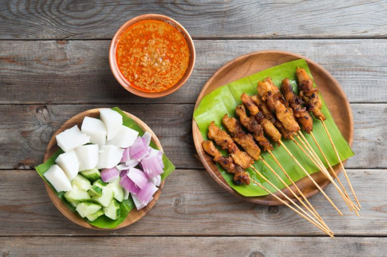 Overhead view Malaysian chicken sate with delicious peanut sauce, ketupat, onion and cucumber on wooden dining table, one of famous local dishes.