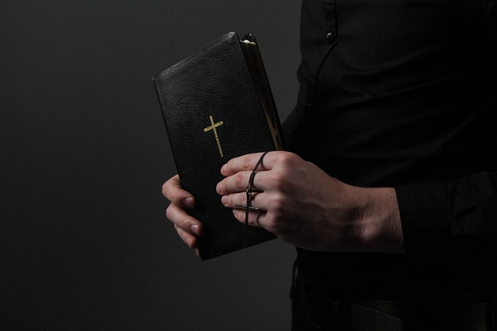 The Bible with the Cross in the Hands of the Priests
