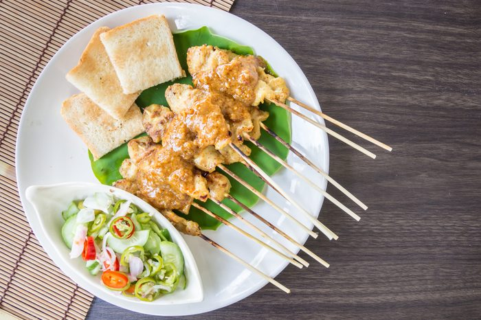 chicken satay with peanut suace, Pickles with are cucumber slices and onions in vinegar,Top view.