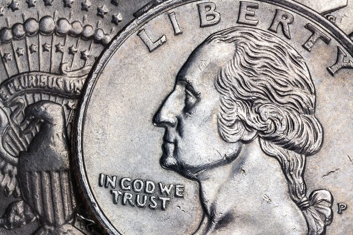 Close-up detail on a United States quarter dollar coin - In God we Trust - Liberty.