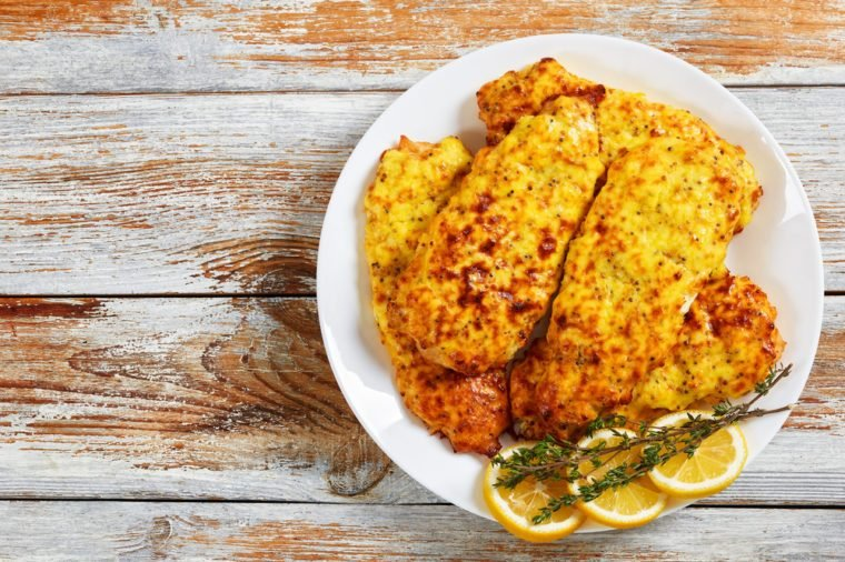 delicious Baked Chicken breast coated with melted emmental cheese and Whole-grain mustard on white plate with thyme and lemon slices, on old wooden table, view from above