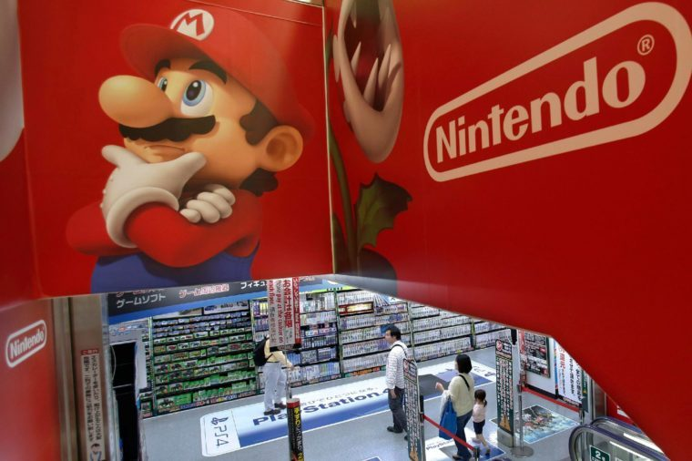 Shoppers walk under the logo of Nintendo and Super Mario characters at an electronics store in Tokyo . Nintendo Co. sank to a loss for the fiscal year ended March as sales of its Wii U game machine continued to lag, but the Japanese manufacturer of Pokemon and Super Mario games promised Wednesday to return to profit this year