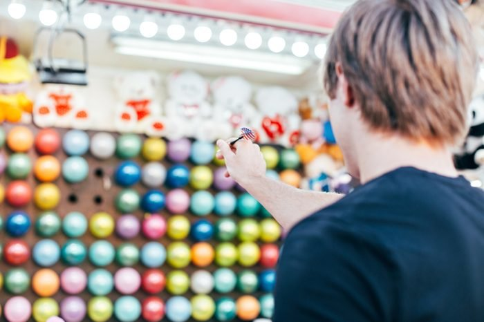 Young man aims at wall of colourful air balloons in order to win teddy bear or plush toy prize for his girlfriend, during romantic date at amusement park or carnival