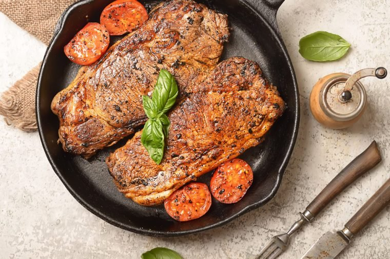 grilled steak and basil on a frying pan
