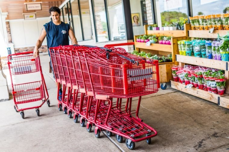 Happy Trader Joe's employee returning shopping carts to the store outside entrance with woman customer