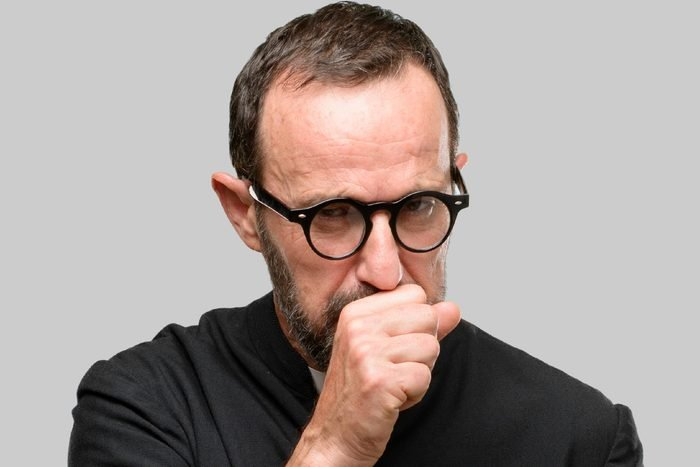 Priest religion man sick and coughing, suffering asthma or bronchitis, medicine concept isolated over blue background