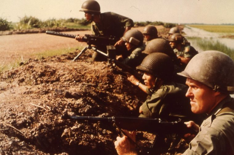U.s. Army Advisors And Vietnamese Infantrymen Await Attack Along Bank Of A Rice Paddy