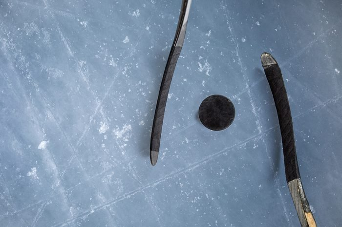 Ice hockey rink scratches surface for texture or background, winter closeup. puck two stick on ice background.