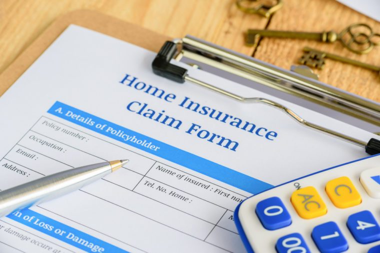 Blue ballpoint pen, two antique brass keys and a home insurance claim from on a plywood clipboard. A blank form is waiting to be completed and signed by a policyholder or an insured person.