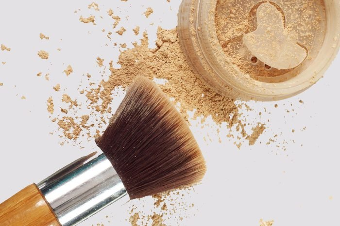 Make up mineral powder in plastic jar with cosmetic brushes