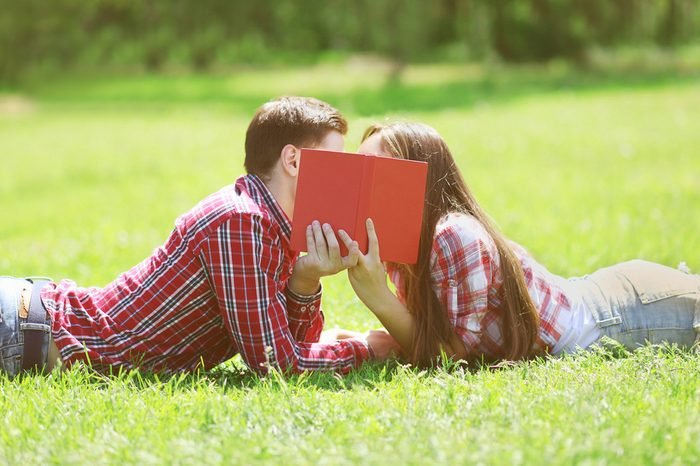 Couple students in love kissing on the grass
