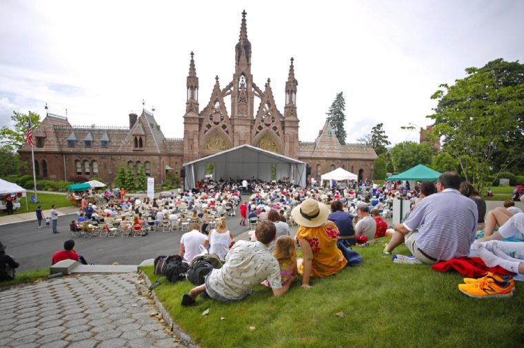 NEW YORK CITY - MAY 30 2016: Green-Wood Cemetery staged it's 28th annual Memorial Day concert by the Symphonic Orchestra at 3rd Street. Visitors fill hilltop overlooking Green-Wood north gate