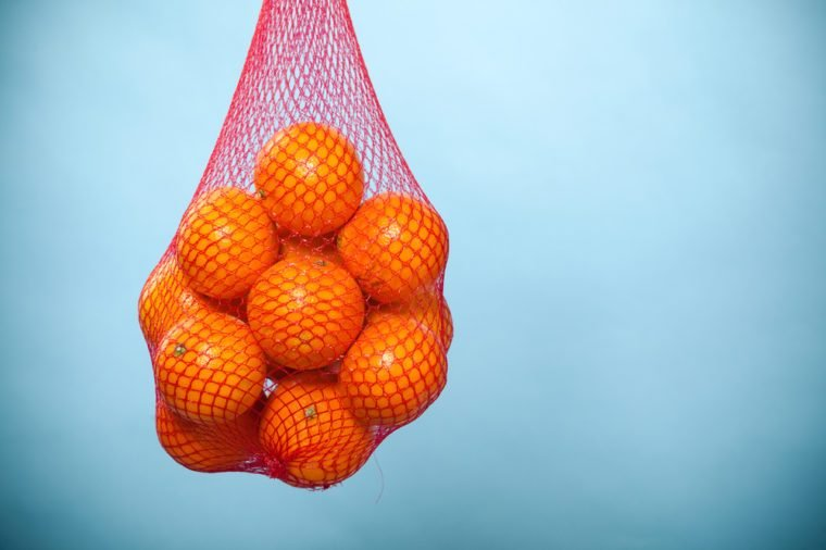 Mesh bag of fresh oranges healthy tropical fruits from supermarket on blue. Food retail.