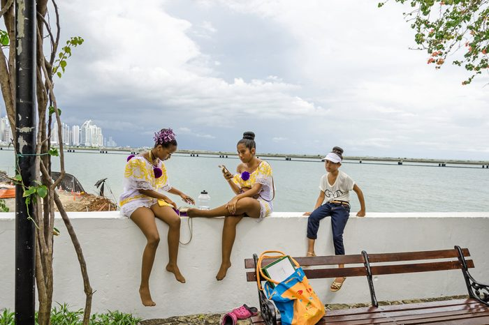 Panama City, Panama - November 3, 2017: Students taking a break after the parade celebrating the Independence Day at Cinta Costera with the skyline of Panama City in a background