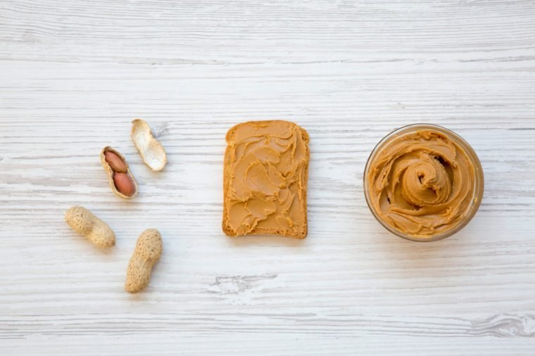 Toast with peanut butter, bowl of peanut butter and peanuts in shells on a white wooden background, top view. Flat lay.