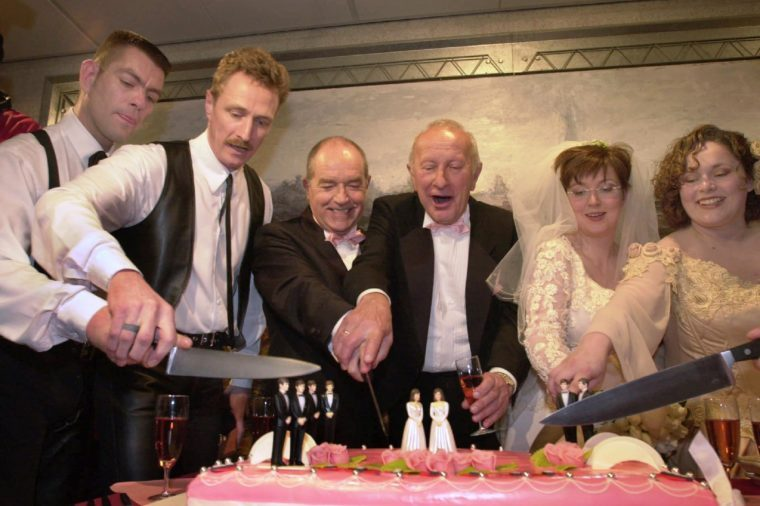 Peter Wittebrood-Lemke, Frank Wittebrood, Ton Jansen, Louis Rogmans, Helene Faasen and Anne-Marie Thus, left to right, cut the wedding cake after exchanging vows at Amsterdam's City Hall early . The pairs were among four gay couples to get married under a new law which took effect April 1, 2001, the world's first such law allowing same-sex marriages with equal rights