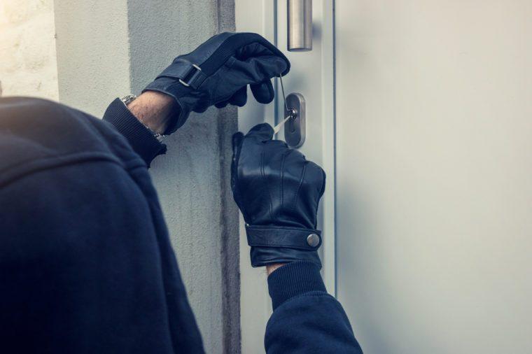 burglar holding Lock-picker to open a housedoor