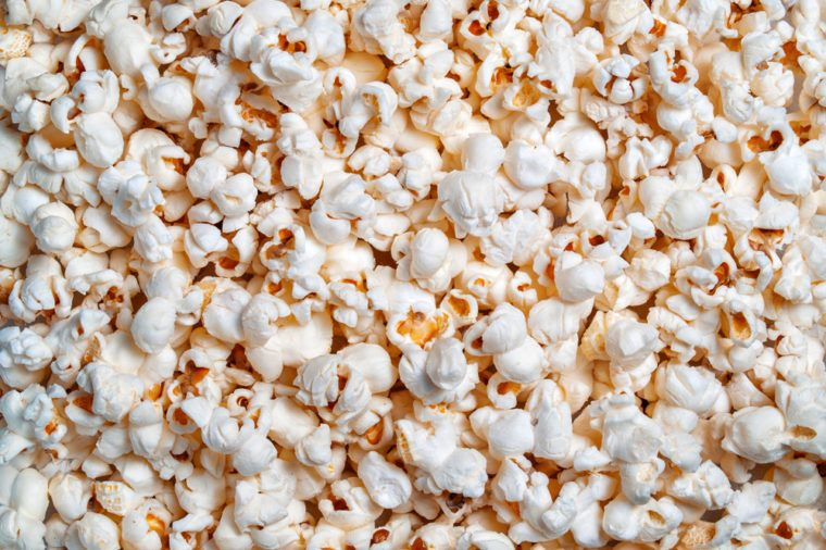 Ready popcorn of corn grains textural background close-up on top