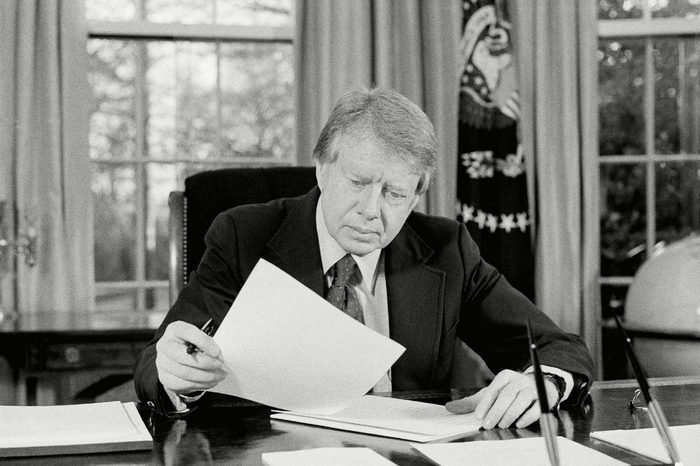 """President Jimmy Carter ponders material in the Oval Office of the White House in Washington in preparation for his televised """"fireside chat"""" with the nation later this evening"""