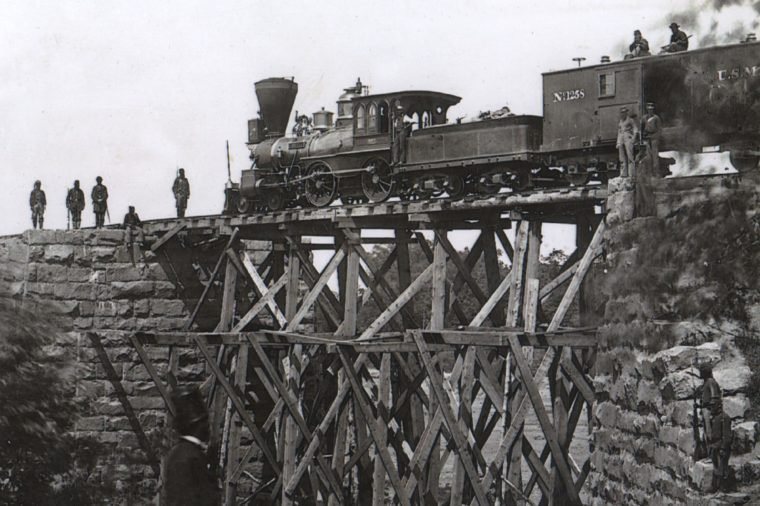 Firefly locomotive engine, built by Harris and Sons 1862, on a trestle of the Orange and Alexandria Railroad (US Military Railroad), Virginia, USA, built by soldiers, photograph by A.J. Russell, 1865.