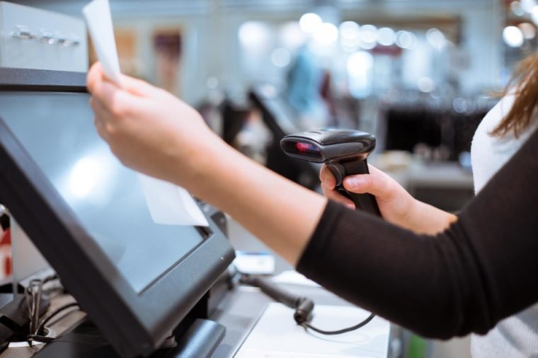 Young woman hands scaning / entering discount / sale on a receipt, touchscreen cash register, market / shop