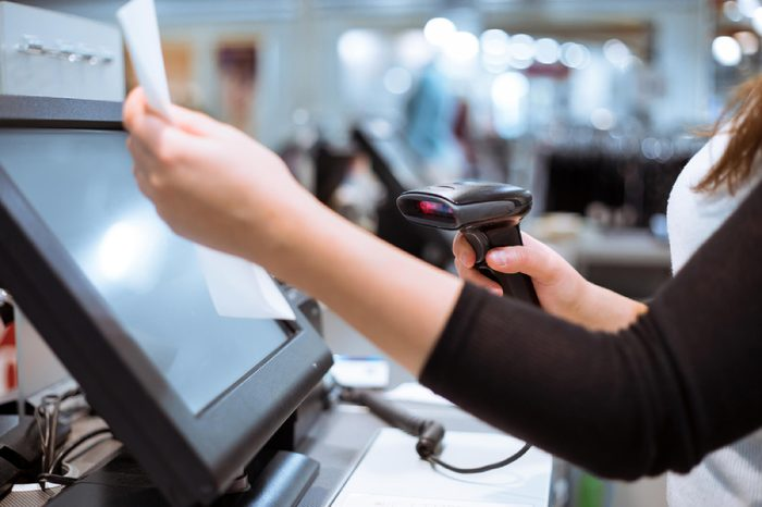 Young woman hands scaning / entering discount / sale on a receipt, touchscreen cash register, market / shop