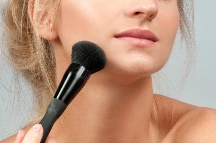 Beauty. Makeup. Beautiful woman applying dry cosmetic tonal foundation on the face using makeup brush.